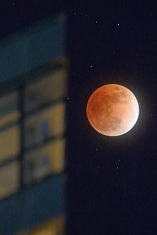 地球の影に覆われ、赤銅色になった月。左は大洗マリンタワー=茨城県大洗町で2018年1月31日午後10時20分、渡部直樹撮影