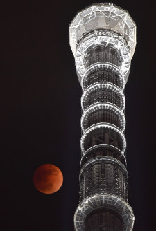 皆既月食で赤銅色に染まる満月。右は東京スカイツリー=東京都墨田区で2018年1月31日午後10時21分、藤井達也撮影