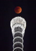 A full moon dyed copper is seen during a total lunar eclipse in Tokyo's Sumida Ward on Jan. 31, 2018. Tokyo Skytree is seen at the bottom. (Mainichi)