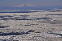 流氷観光するオーロラ号。後方は羅臼岳=北海道・オホーツク海沖で2018年2月2日、本社機「希望」から宮本明登撮影