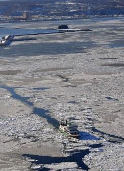 流氷観光するオーロラ号。後方は網走市=北海道・オホーツク海沖で2018年2月2日、本社機「希望」から宮本明登撮影