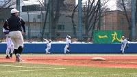 キャッチボールする東大野球部の選手。スローガン「一丸」の文字が掲げられている=東京都文京区の東大球場で、岡本同世撮影