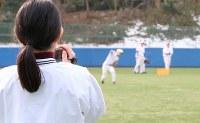 外野の守備練習を撮影するマネジャーの神﨑萌絵さん。4月で3年生になる神崎さんは、神宮球場での六大学野球リーグ戦場内アナウンスデビューを控えている。「全国に配信されるので、ちょっと緊張します。練習しておかないと」=東京都文京区の東大球場で、岡本同世撮影