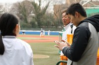 浜田一志監督の指示を受け、すぐにスマートフォンから連絡する中川さん。「即やる、を心がけています」=東京都文京区の東大球場で、岡本同世撮影