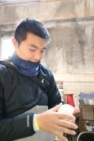 選手が練習中に食べるおにぎりを作る主務の中川さん。最上級生になっても、グラウンドに来たときは積極的に動く=東京都文京区の東大球場で、岡本同世撮影