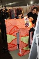 ボランティアのコーディネーターたちに案内されながら、楽しそうに着物を選ぶ新成人ら=横浜市中区で、2018年2月4日午前11時20分、国本愛撮影