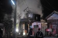 自衛隊ヘリが墜落した現場付近で燃える民家を消火する消防隊員=佐賀県神埼市で2018年2月5日午後7時35分、徳野仁子撮影