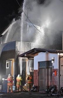 自衛隊ヘリが墜落した現場付近で燃える民家を消火する消防隊員=佐賀県神埼市で2018年2月5日午後7時41分、徳野仁子撮影