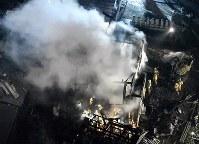 陸自ヘリが墜落した現場付近で炎上する民家=佐賀県神埼市で2018年2月5日午後7時57分、本社ヘリから上入来尚撮影