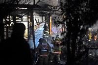 陸自ヘリコプターが墜落した現場付近の住宅の消火活動を続ける消防隊員ら=佐賀県神埼市で2018年2月5日午後8時16分、矢頭智剛撮影