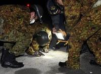 陸自ヘリコプターが墜落した住宅近くの道路を調べる自衛隊員ら=佐賀県神埼市で2018年2月5日午後9時37分、矢頭智剛撮影
