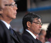 Susumu Inamine, right, maintains a stern expression beside Okinawa Gov. Takeshi Onaga, left, upon learning of his mayoral election loss to newcomer Taketoyo Toguchi in Nago, Okinawa Prefecture, on Feb. 4, 2018. (Mainichi)