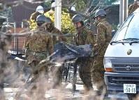 墜落現場から陸自ヘリコプターのものと見られる部品を運び出す自衛隊員=佐賀県神埼市で2018年2月6日午前10時18分、徳野仁子撮影