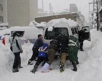 大雪で立ち往生した車を押す人たち=福井市で2018年2月6日午前11時7分、近藤諭撮影