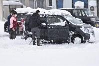 金沢市内では、雪にはまり動けなくなった車を、協力して救出する光景があちこちで見られた=金沢市薬師堂町で2018年2月6日午前10時47分、日向梓撮影