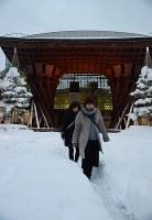 積もった雪の間にできた道を歩く人たち=金沢市木ノ新保町のJR金沢駅東口で2018年2月6日午後5時24分、久木田照子撮影