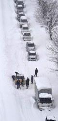 大雪のため、国道8号で動けなくなった乗用車の周囲を除雪する人たち=福井市で2018年2月6日午後2時57分、本社ヘリから加古信志撮影