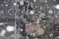 雪が降る中、立ち往生した車の運転手におにぎりを配る自衛隊員=福井県あわら市熊坂で2018年2月6日午後6時24分、立野将弘撮影