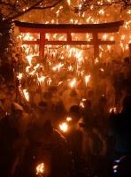 たいまつを手に勢いよく駆け下りる「上り子」たち=和歌山県新宮市で2018年2月6日午後7時55分、猪飼健史撮影