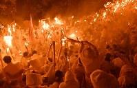 たいまつに炎をともす「上り子」たち=和歌山県新宮市で2018年2月6日午後7時48分、猪飼健史撮影
