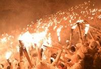 たいまつに炎をともす「上り子」たち=和歌山県新宮市で2018年2月6日午後7時52分、猪飼健史撮影