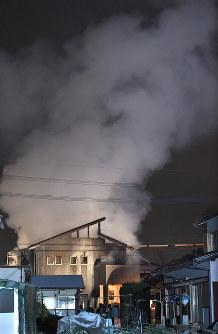 煙を上げて燃える自衛隊ヘリが墜落した現場付近の民家=佐賀県神埼市で2018年2月5日午後6時39分、徳野仁子撮影