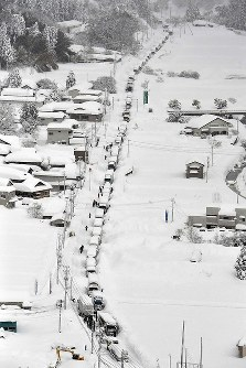 Vehicles are seen stranded in the snow piled up along National Route 8 from a Mainichi Shimbun helicopter in Awara, Fukui Prefecture, on Feb. 7, 2018. (Mainichi)