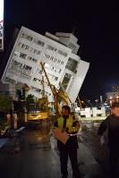 地震で大きく傾いた雲門翠堤ビル。数十人の住民の行方がわかっておらず、捜索活動が続けられている=台湾・花蓮市で2018年2月7日午後7時40分、林哲平撮影