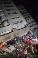 地震で大きく傾いた雲門翠堤ビル。数十人の住民と連絡が取れておらず、捜索活動が続けられている=台湾・花蓮市で2018年2月7日午後7時40分、林哲平撮影