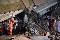 地震で大きく傾いた雲門翠堤ビル。数十人の住民と連絡が取れておらず、捜索活動が続けられている=台湾・花蓮市で2018年2月7日午後7時45分、林哲平撮影