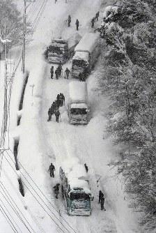 車両が立ち往生する国道8号で除雪作業をする自衛隊員ら=福井県あわら市で2018年2月7日午前9時33分、本社ヘリから小関勉撮影