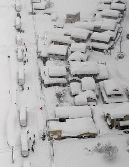 車両が立ち往生する国道8号で除雪作業をする自衛隊員ら=福井県あわら市で2018年2月7日午前9時40分、本社ヘリから小関勉撮影