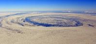 沖で渦巻く流氷。後方右は知床岬=北海道・オホーツク海で2018年2月2日午後2時34分、本社機「希望」から宮本明登撮影