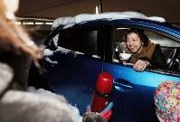 記録的な大雪で国道8号で多くの車両が立ち往生する中、地元住民からコーヒーの差し入れを受ける運転手の男性=福井県坂井市で2018年2月7日午後8時15分、幾島健太郎撮影