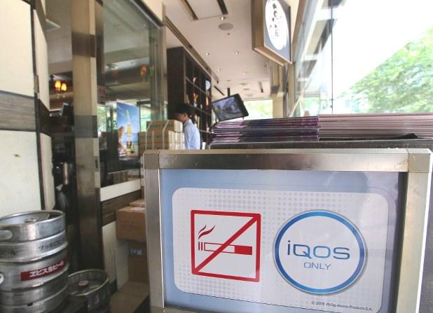 「禁煙」だが「アイコスのみ可」の印を入り口に掲げた東京都内のカフェ