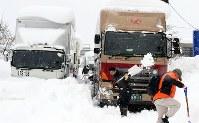 国道8号で立ち往生するトラックの列の前で除雪をする男性=福井県坂井市で2018年2月8日午前10時35分、幾島健太郎撮影