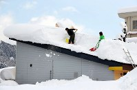 屋根の上の除雪作業をする人たち=福井県勝山市で2018年2月8日午後1時47分、幾島健太郎撮影