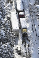 大雪の影響で国道8号線に立ち往生した車と除雪する人ら=福井県あわら市で2018年2月8日午後0時48分、本社機「希望」から