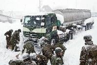 国道8号で立ち往生するトラックの除雪作業をする自衛隊員ら=福井県坂井市で2018年2月8日午後4時40分、幾島健太郎撮影