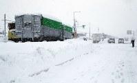 福井市方面行き(手前)は除雪が進んだものの、あわら市方面行き(奥)はトラックの立ち往生が続く国道8号=福井県坂井市で2018年2月8日午後4時43分、幾島健太郎撮影