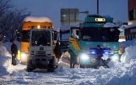 国道8号で立ち往生するトラックの列の前で、日が落ちてからもヘッドライトの明かりを頼りに除雪をする男性=福井県坂井市で2018年2月8日午後5時48分、幾島健太郎撮影
