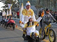 トーチを手に自転車で聖火をリレーする参加者=韓国・江陵で2018年2月8日午前9時12分、佐々木順一撮影