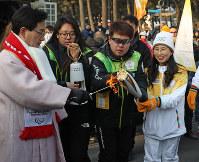 スタート地点で聖火をトーチにつけるランナーら=韓国・江陵で2018年2月8日午前9時10分、佐々木順一撮影