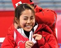 スキージャンプ女子ノーマルヒルの練習後、ビブスがうまく脱げずにスタッフに手伝ってもらう高梨沙羅=アルペンシア・ジャンプセンター2018年2月8日、山崎一輝撮影