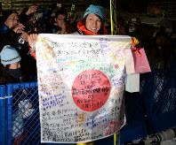 観客にもらった寄せ書きを手に笑顔を見せる葛西紀明=札幌市の大倉山ジャンプ競技場で2014年1月25日、木葉健二撮影