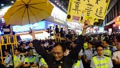 「真の普通選挙を」と書いたボードを持ち警官隊の前に立つ男性=香港で2014年11月26日、隅俊之撮影