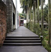 鏡花園の景観。れんが、石、カキ殻など異なる素材を使った壁と亜熱帯の植物や野菜が植えられた庭が向かい合っている