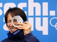 【ソチ五輪】メダルセレモニー後、銀メダルの透明な部分からカメラをのぞく葛西紀明=ロシア・ソチの五輪公園で2014年2月16日、貝塚太一撮影