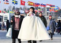 厳重な防寒対策をして開会式会場に入る人たち=平昌五輪スタジアムで2018年2月9日午後、宮間俊樹撮影