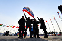 開会式会場への入場前にロシアの旗を手に記念撮影するロシアから来た観客たち=平昌五輪スタジアムで2018年2月9日午後、宮間俊樹撮影